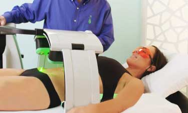 A woman quickly removing fat from her stomach area with Emerald Laser